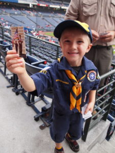 A Scout passes out National Anthem Instructions
