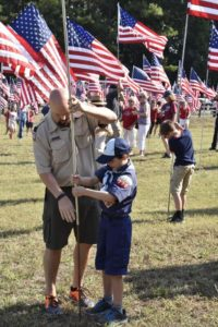 A Scout and his dad post a flag in the Field of Flags