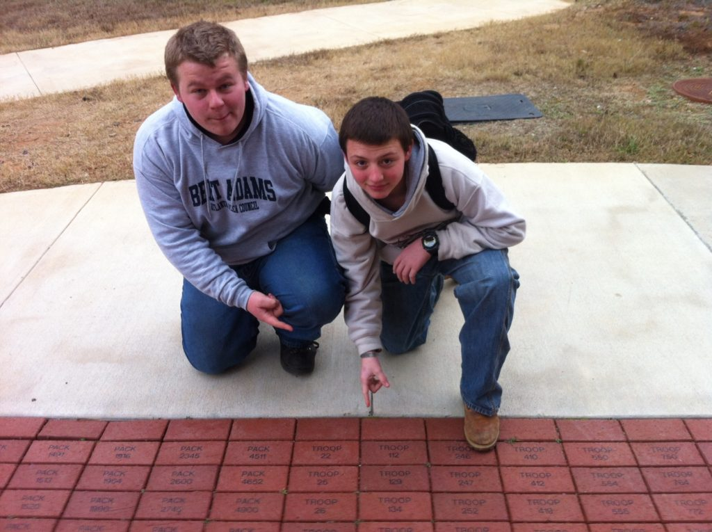 Kendall points out his Troop's brick at Bert Adams