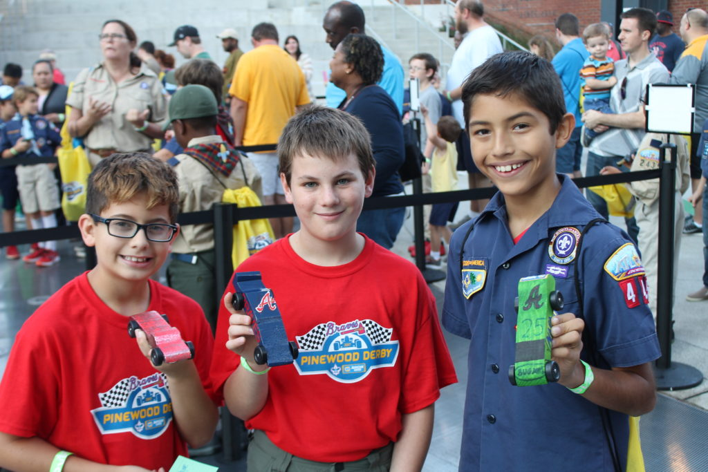 Three Cub Scouts hold up their Pinewood Derby Cars