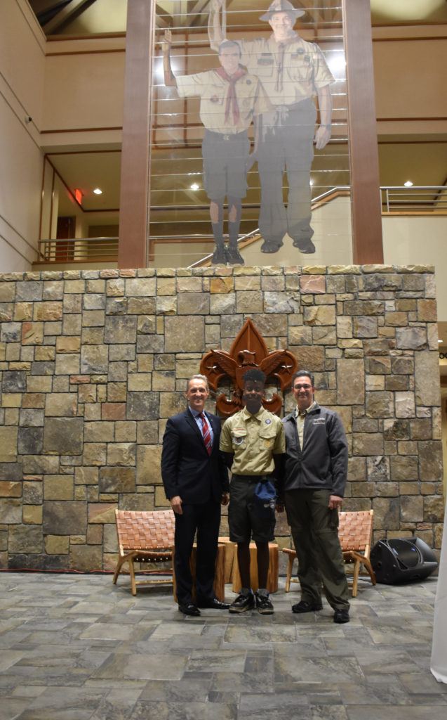 Tion with Scout Executive/CEO Tracy Techau and volunteer Greg Becker in front of the monument at the VSC