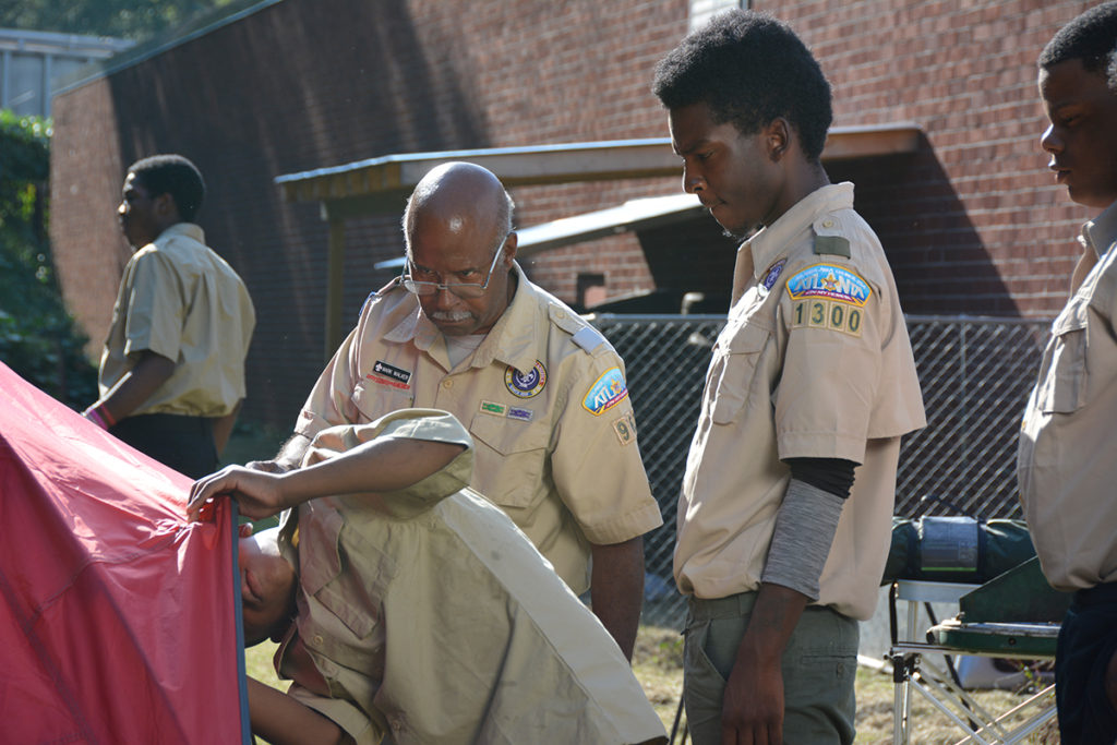 Program Specialist Mark Walker oversees Scouts setting up a tent.
