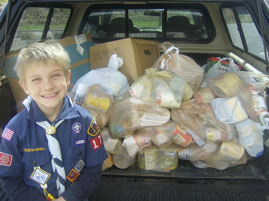 A Scout collects canned goods for Scouting for Food