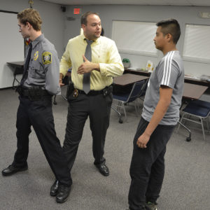 Sargent Snively coaches two Explorers on the proper technique for handcuffing.