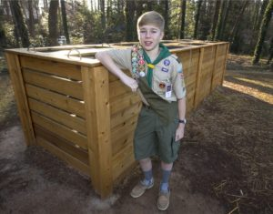 Eagle Scout Ben Bird poses next to the composting bins he built for his Eagle Scout project