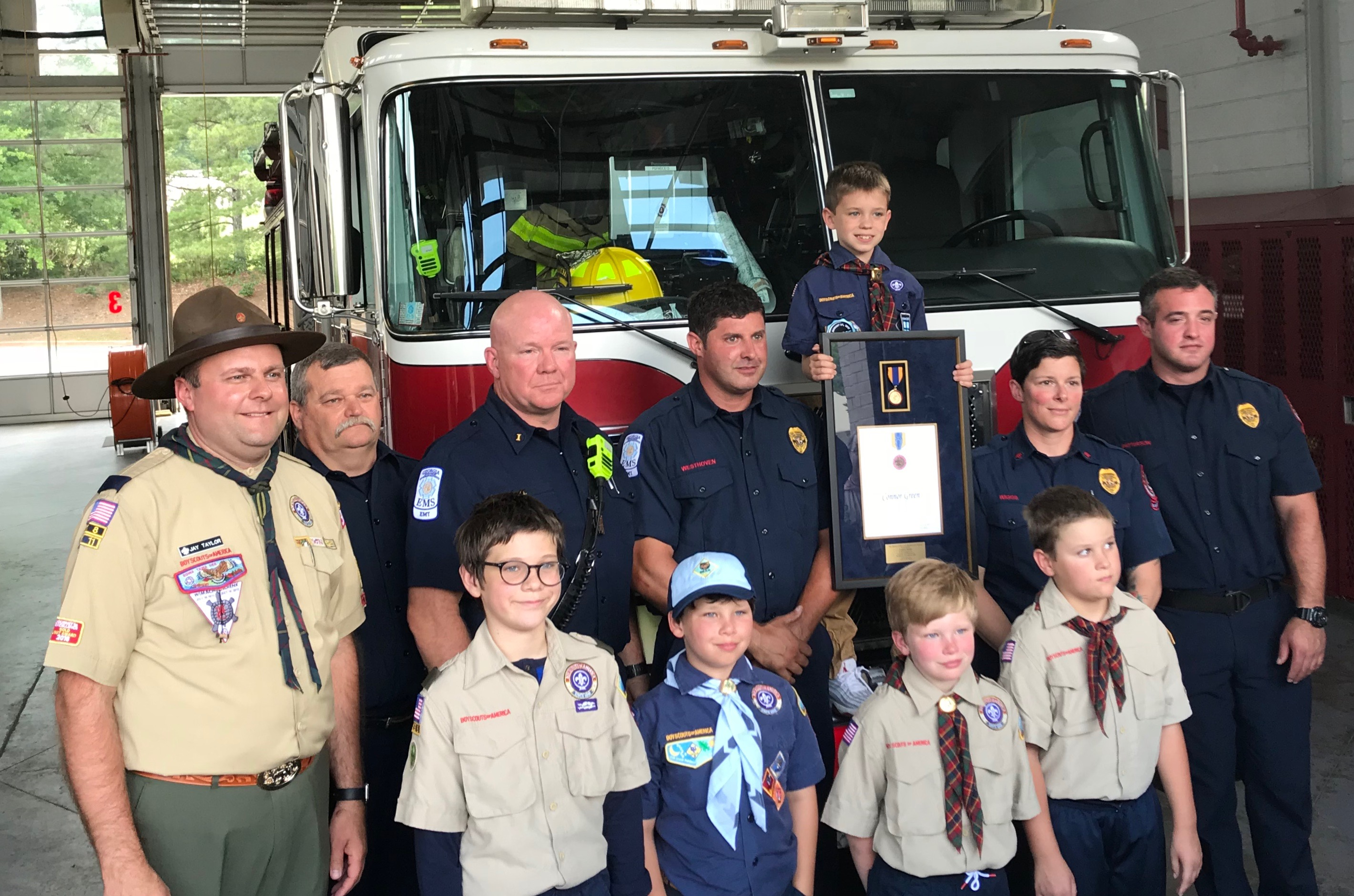 Connor holds up his Medal of Merit alongside local firefighters and members of Pack 353