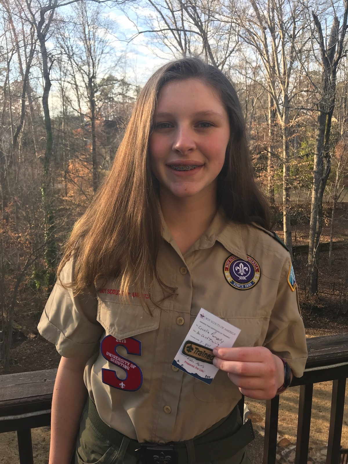 Cecilia holding her 'Trained' Scouting badge.